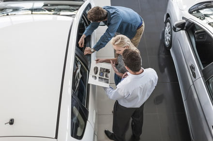 car dealer showing brochure to young couple in showroom 440x292 c - COVID-19 may already be causing new car sales to fall -  ایگر