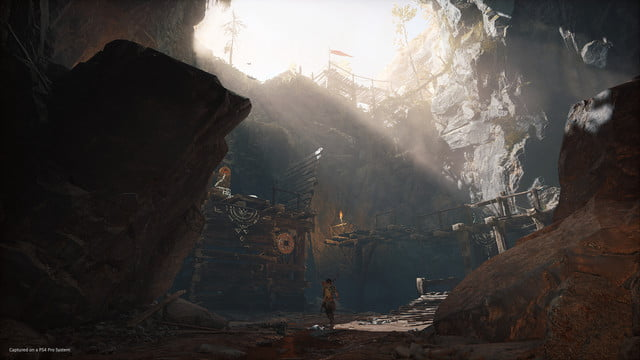 God of War Review | Atreus walking through a large forest ravine environment