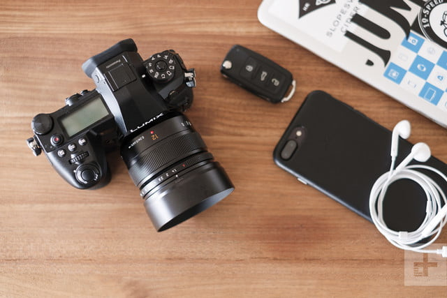 Panasonic Lumix G9 Review | Lifestyle shot of the camera sitting on a table with a phone and keys