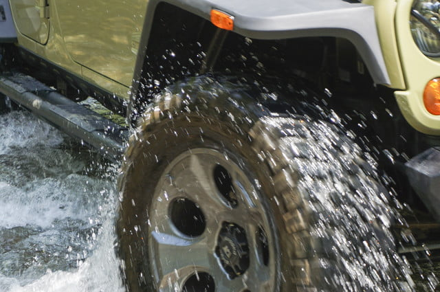 A Jeep Wrangler Unlimited's wheel driving through water